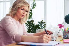 Marvelous female writing while working in laptop Royalty Free Stock Photos