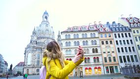 Marvelous girl calls up in Videocall and shares impressions, standing in center of European city against background of. Pretty female chatters in videocall with stock video