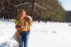 Marvelous kindhearted woman standing in snowdrift and looking into the distance with yellow snowdrops in hand royalty free stock photography