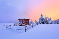 On the lawn there is wooden church covered with snow high on the mountains. Royalty Free Stock Photos