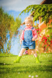 Marvelous little girl plays with on green spring grass Royalty Free Stock Photography