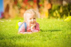 Marvelous little girl plays with on green spring grass Stock Images