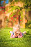 Marvelous little girl plays with on green spring grass Royalty Free Stock Photos