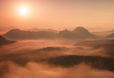 Marvelous red daybreak. Misty daybreak in a beautiful hills. Peaks of hills are sticking out from foggy background, the fog is red Stock Photos