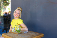 Marvelous young girl smiling broadly, looks away, laughing, sits Royalty Free Stock Photos