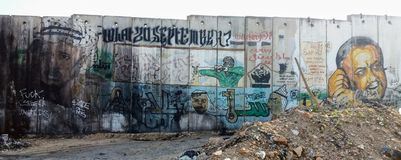 West Bank barrier with murals. Marwan Barghouti, young Yasser Arafat and fighter shooting love, painted on Palestinian-Israeli separation wall at Qalandia royalty free stock photo