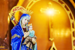Mary and baby in the church. Mary and baby doll in her arms standing in the church with warm light tone Royalty Free Stock Photography