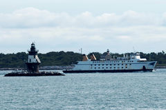 The Mary Ellen ferry passing the Orient Point Lighthouse. Orient Point, New York, USA – 27 July 2017: The Mary Ellen ferry ship is passing the Orient Point Stock Photos