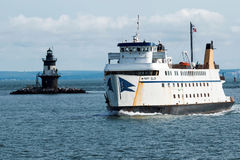 The Mary Ellen passing the Orient Point Lighthouse. Orient Point, New York, USA – 27 July 2017: The Mary Ellen ferry ship is passing the Orient Point Royalty Free Stock Images