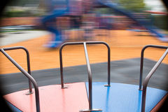 Merry go around / roundabout. The viewer is on the merry-go-around spinning and seeing the playground go by Stock Photography