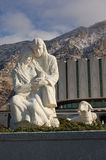 Mary, Joseph and Jesus statue. White statue of Mary, Joseph and Jesus with sheep, building and mountains in background royalty free stock photo