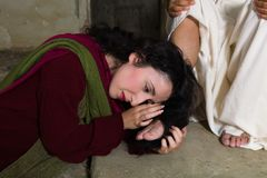 Mary Magdalene drying Jesus feet with her hair. Mary Magdalene crying of shame and embalming Jesus` feet stock photos