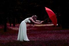 Mary Poppins, современная концепция моды Кавказская белая женская модель стоя с красными зонтиком и маской противогаза стоковая фотография