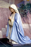 Mary Praying. Statue of Mary kneeling in prayer Stock Photo