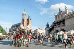 Cracow main square with tourists and horse carriage, Cracow, Pol. Mary`s Church and Cloth`s Hall with tourists and horse carriage, Cracow, Poland Royalty Free Stock Photo