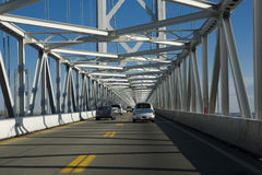 Maryland Bridge. Several cars travel under a bridge. This image focuses on the bridge, the road and distant cars are blurry due to motion stock photos