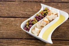 Marynowane oliwki, chlebów kawałki i oliwa z oliwek w półmisku, Fotografia Stock