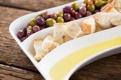 Marynowane oliwki, chlebów kawałki i oliwa z oliwek w półmisku, Obrazy Stock