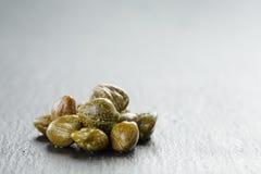Marynowani kapary w oliwnym pucharze na łupku wsiadają obraz stock
