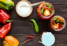 Marynowani warzywa w słoju szkło: gorąca czerwień i zieleni pieprze z cukierem fotografia stock