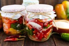 Marynowani warzywa w słoju szkło: gorąca czerwień i zieleni pieprze z cukierem obrazy stock
