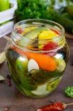 Marynowani warzywa w szklanym słoju Asortowani ogórki, pieprze, marchewki, patissons, zucchini obrazy royalty free