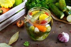 Marynowani warzywa w szklanym słoju Asortowani ogórki, pieprze, marchewki, patissons, zucchini zdjęcie royalty free
