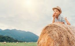 Marzący chłopiec w słomianym kapeluszu kłama na rolki haystack Zdjęcia Royalty Free