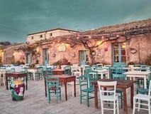 Marzamemi Sicilien - Januari 01, 2018: Sikt av en typisk restaurang i Marzamemi på solnedgången Marzamemi Sicilien fotografering för bildbyråer