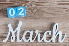 Marzec 2nd Dzień 2 marszu miesiąc, dzienny kalendarz na drewnianym stołowym tle z rzeźbiącym tekstem Wiosna czas… wzrastał liście Fotografia Royalty Free