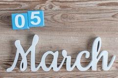 Marzec 5rd Dzień 5 marszu miesiąc, dzienny kalendarz na drewnianym stołowym tle z rzeźbiącym tekstem Wiosna czas… wzrastał liście Obraz Stock