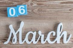 Marzec 6th Dzień 6 marszu miesiąc, dzienny kalendarz na drewnianym stołowym tle z rzeźbiącym tekstem Wiosna czas… wzrastał liście Zdjęcia Royalty Free