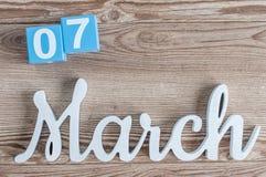 Marzec 7th Dzień 7 marszu miesiąc, dzienny kalendarz na drewnianym stołowym tle z rzeźbiącym tekstem Wiosna czas… wzrastał liście Zdjęcia Royalty Free