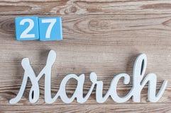 Marzec 27th Dzień 27 marszu miesiąc, dzienny kalendarz na drewnianym stołowym tle z rzeźbiącym tekstem Wiosna czas… wzrastał liśc Fotografia Stock