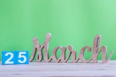 Marzec 25th Dzień 25 miesiąc, dzienny drewniany kalendarz na stole i zieleni tło, Wiosna czas, opróżnia przestrzeń dla teksta Zdjęcia Stock