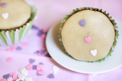 Marzipan cupcake decorated with icing and pink hearts Stock Photos
