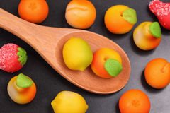 Marzipan fruit shapes in a wooden spoon Stock Images