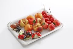 Marzipan, ladybird, may bug, peaches, strawberries, cherries on paper plate Stock Photo