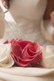 Marzipan red rose on wedding cake. Bride cutting with knife marzipan red rose on wedding cake Stock Image