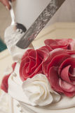 Marzipan red rose on wedding cake. Cutting with knife marzipan red rose on wedding cake Royalty Free Stock Images