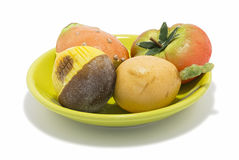 Marzipan sweets. Chestnut, prickly pear, tomato, medlar on a green dish Royalty Free Stock Images