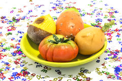 Marzipan sweets. Chestnut, prickly pear, tomato, medlar, surrounded by so many letters Royalty Free Stock Photo