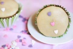 Marzipankleiner kuchen verziert mit Zuckerglasur und rosa Herzen Stockfotos