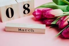 8 marzo concetto felice di giorno del ` s delle donne Con il calendario di blocco di legno ed i tulipani rosa su fondo rosa Copi  Immagine Stock