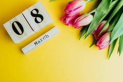 8 marzo concetto felice di giorno del ` s delle donne Con il calendario di blocco di legno ed i tulipani rosa su fondo giallo Cop Fotografie Stock