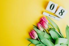 8 marzo concetto felice di giorno del ` s delle donne Con il calendario di blocco di legno ed i tulipani rosa su fondo giallo Cop Fotografia Stock
