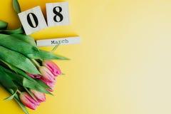 8 marzo concetto felice di giorno del ` s delle donne Con il calendario di blocco di legno ed i tulipani rosa su fondo giallo Cop Immagine Stock