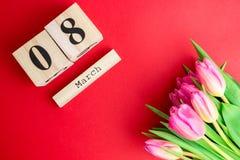 8 marzo concetto felice di giorno del ` s delle donne Con il calendario di blocco di legno ed i tulipani rosa su fondo rosso Copi Fotografie Stock