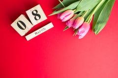 8 marzo concetto felice di giorno del ` s delle donne Con il calendario di blocco di legno ed i tulipani rosa su fondo rosso Copi Fotografie Stock Libere da Diritti