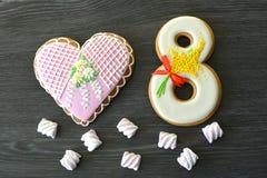 8 marzo dolci pan di zenzero e fondo di legno grigio della tavola del cuore Fotografia Stock